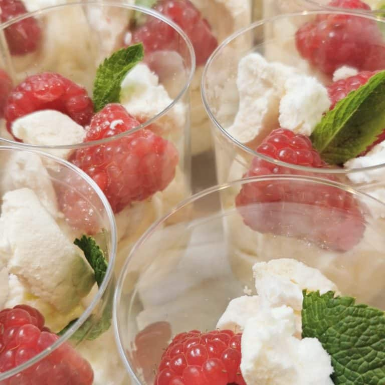 Witte chocolade mousse dessert met verse frambozen en meringue